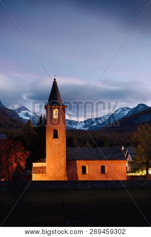 Christianity church on Sils village (near lake Sils) in Swiss Alps. Orange light on building and snowy mountains on background. Switzerland, Maloja region, Upper Engadine. Landscape photography