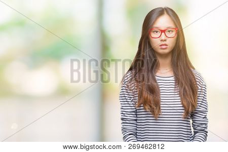 Young asian woman wearing glasses over isolated background with serious expression on face. Simple and natural looking at the camera.