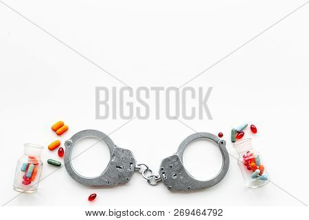 Arrest For Illegal Purchase, Possession And Sale Drugs Concept. Drugs As Pills Near Handcuff On Whit
