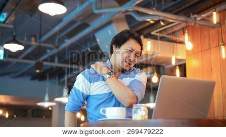 Asian Businessman In Casual Suit Working Which Have Symptom Is Neck Pain, Backache, Headache At Co-w