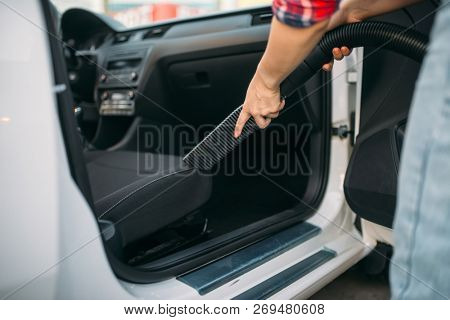 Woman cleans car interior with vacuum cleaner
