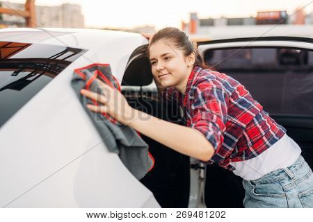 Woman wipes automobile, self-service car wash