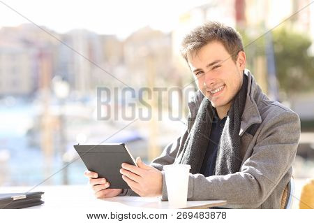 Happy Self Employed Holding A Tablet Looking At You Sitting In A Coffee Shop Terrace Of A Coast Town