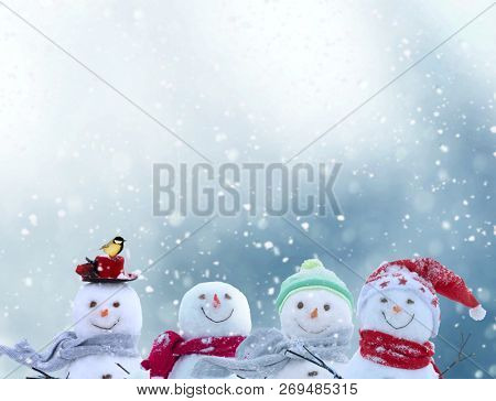 Merry christmas and happy new year greeting card with copy-space.Happy snowmen standing in winter christmas landscape.Snow background