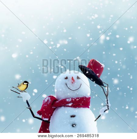 Merry christmas and happy new year greeting card with copy-space.Happy snowman standing in winter christmas landscape.Snow background