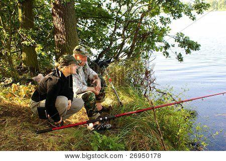 Senior fisherman fishing with daughter