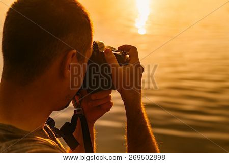 Male Photographer Taking Photo Of Riverside Sunset With Professional Camera Outdoors. Man Photograph