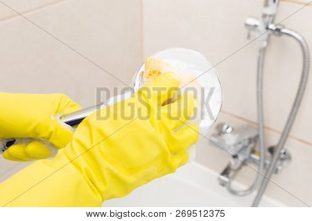 Person Wearing Yellow Gloves Using Orange Sponge With Foam For Cleaning Inox Shower Head