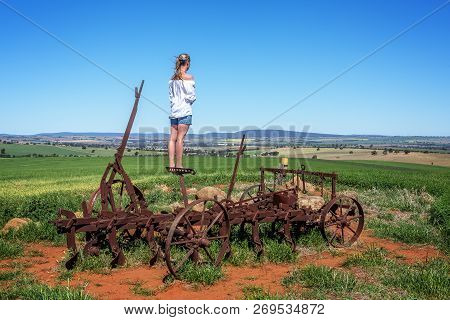 Standing On A Rusting Antique Farm Tiller On The Hillside Observing The Crops Progress And With View
