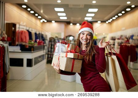 Happy Girl Shopping Gifts In Mall On Christmas Sale. New Year Holidays Shopping Idea Concept. Smilin
