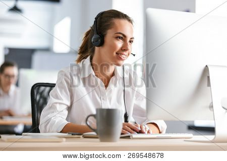Photo of a happy cheerful business woman in office callcenter working with computer wearing headphones.