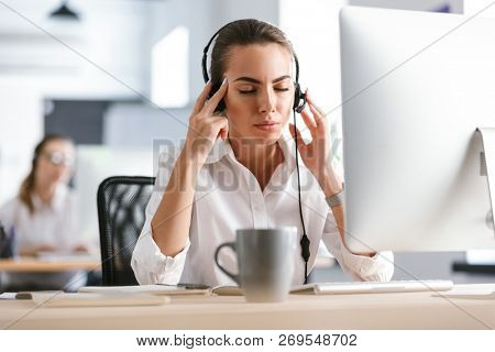 Image of a displeased business woman with headache in office callcenter working with computer wearing headphones.