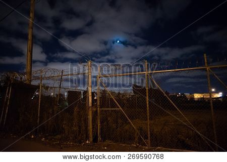 Dark and gritty rusty barbwire fence gate by an abandoned empty urban city lot with the moon at night
