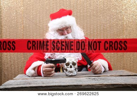 Santa Claus. Santa Crime Scene. Santa Claus holds a Gun and Knife to a Human Skull for an unexpected Evil Santa Photo Shoot. Crime Scene do not cross.