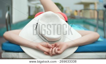 An Unrecognizable Slim Busty Woman In A Big White Hat And A Pink Bikini Is Lying On A Chaise Lounge