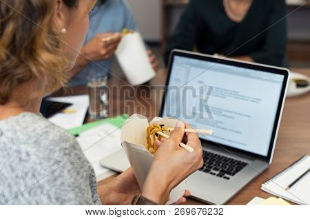 Business woman eating instant noodles with chopsticks while working at office. Casual businesswoman reading document on laptop while eating take away food. Executive working during lunch break.