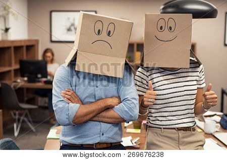Business man and businesswoman covering face with cardboard box showing happy and sad face. Businessman wearing sad face near his colleague with positive expression. Young woman with thumbs up.