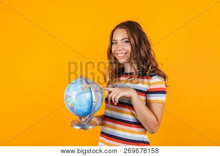 Portrait of a pretty young girl standing isolated over yellow background, pointing finger at a globe