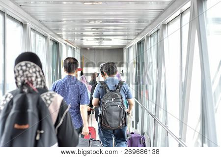 People Boarding To Aircraft In Airport Using Boarding Bridge.