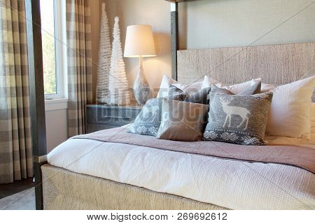 Elegant bedroom with reindeer and peace cushions on the bed for the Christmas holiday season.