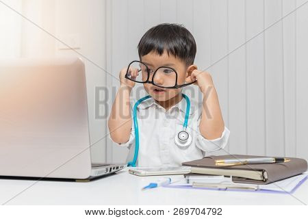 Young Asian Boy Playing Doctor And Using Computer Laptop.