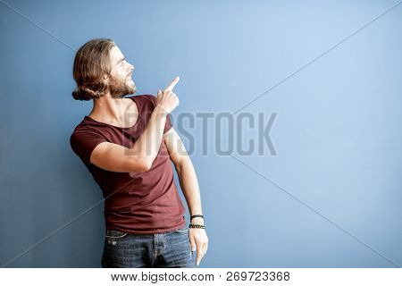 Portrait Of A Young Caucasian Bearded Man With Long Hair Dressed In T-shirt Showing With Hand On The