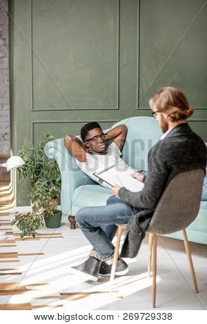 Young Afro Ethnicity Man Having A Serious Conversation With Psychologist Lying On The Comfortable Co