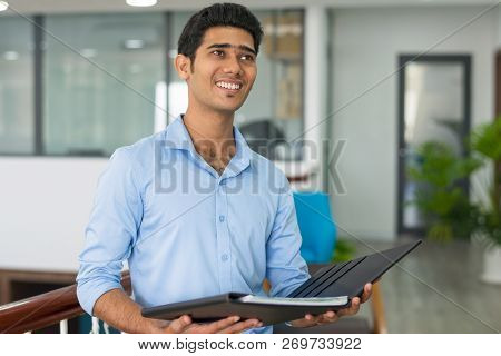 Cheerful Handsome Indian Businessman With Documents Thinking About Company Development. Positive Amb