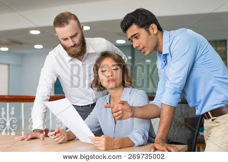 Business Colleagues Helping Newcomer To Complete Job Application Form. Young Office Employee Having