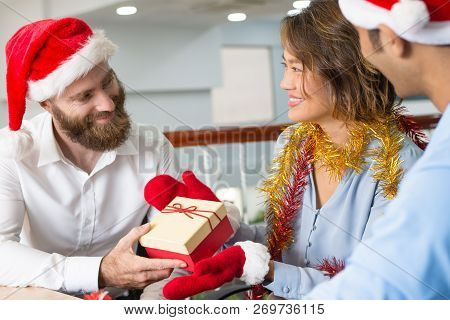 Joyful Business Colleagues Exchanging Gifts During Office Christmas Party. Cheerful Bearded Man In S