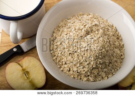Raw Scottish Oatmeal, Cold Milk In A Mug And Apple