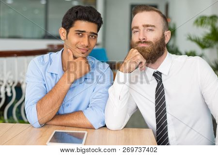 Successful Business Team Of Two Posing. Two Young Businessmen Sitting In Coworking Space, Leaning Ch