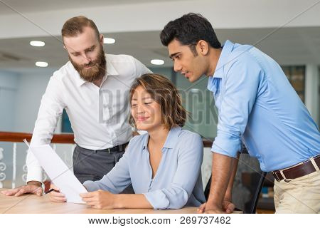 Team Of Managers Satisfied With Sales Report. Young Business Expert And Her Male Colleagues Reading