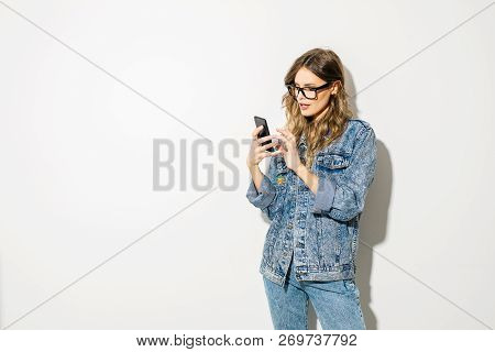 Young Trendy Woman In Jeans Outfit Posing On White With A Cellphone