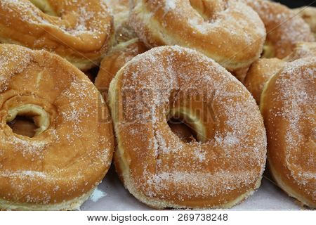 many sugary donuts on the counter of a pastry shop poster