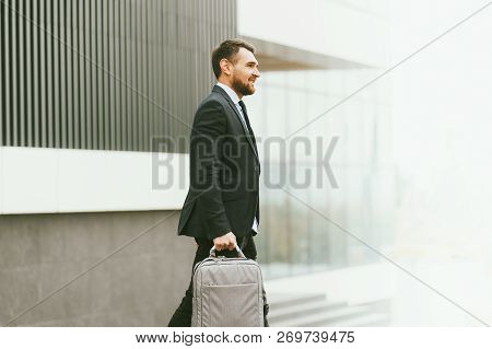 Portrait Of Handsome Modern Businessman. Confident Young Man In Full Suit Walking On Street In City