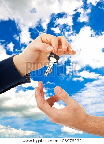 Hand passing a key to another one against a blue vivid sky