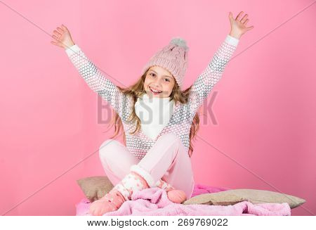 Keep Warm And Comfortable. Kid Girl Wear Knitted Hat Relaxing Pink Background. Child Long Hair Warm