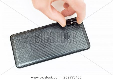 A Man Is Installing A Protective Glass On The Back Lens Of The Smartphone.