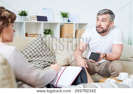 Furious Emotional Handsome Bearded Man Sitting On Sofa With Cushions And Showing Video Of Wives Adul