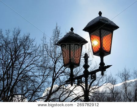 Silhouette Of Vintage Street Lamp On Background Of Bare Tree Branches And Blue Sky. The Sun Shines T