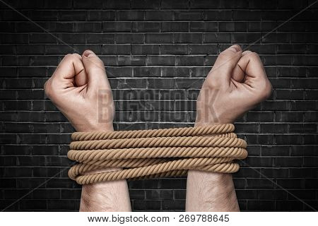 Two Bound Strong Male Arms Struggling To Break A Strong Natural Rope On A Black Brick Background.