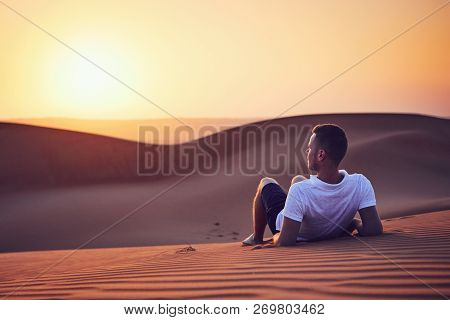 Idyllic Sunrise In Desert. Young Man Contemplation On Sand Dune. Wahiba Sands In Oman.