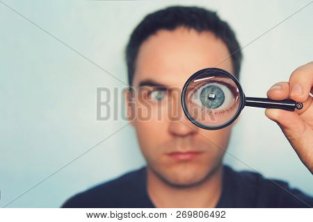 Potrait Of Young Man Looking Through Magnifying Glass On White Blurred Background. View To Male Blue