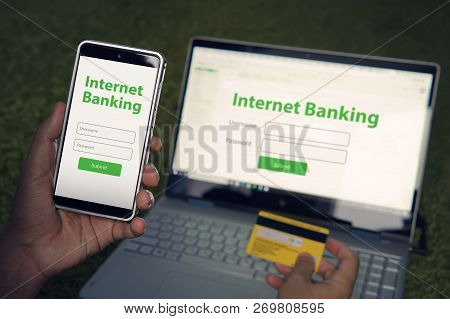 Man Browsed Homepage Of Internet Banking Service On His Smartphone And Laptop Holding Credit Card. O