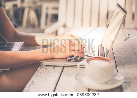 Image Of Women Working On Her Computer Laptop In Coffee Shop With Cappuccino Coffee On White Table.