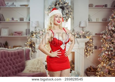 Sexy woman in a red dress is smiling temptingly near a New Year tree. poster