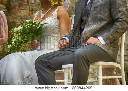 Newly-weds Couple Sitting On The White Wedding Chairs Listening The Registrar And Waiting For Their