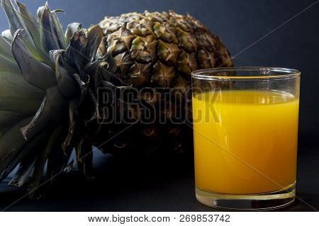 Pineapple And Glass Of Juice Isolated On Dark Black Background. The Pineapple Ananas Comosus Is A Tr