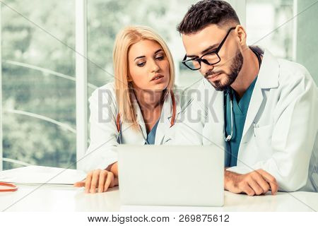 Two Doctors Partner Works At Office In Hospital.
